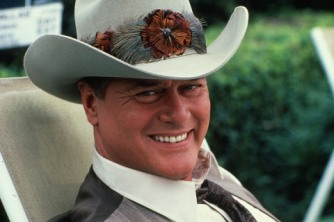 A still from the American television series 'Dallas' shows actor Larry Hagman, who plays John Ross 'J.R.' Ewing Jr., as he sits in a lawnchair dressed in a waistcoat and Stetson, June 1982. (Photo by CBS Photo Archive/Getty Images)
